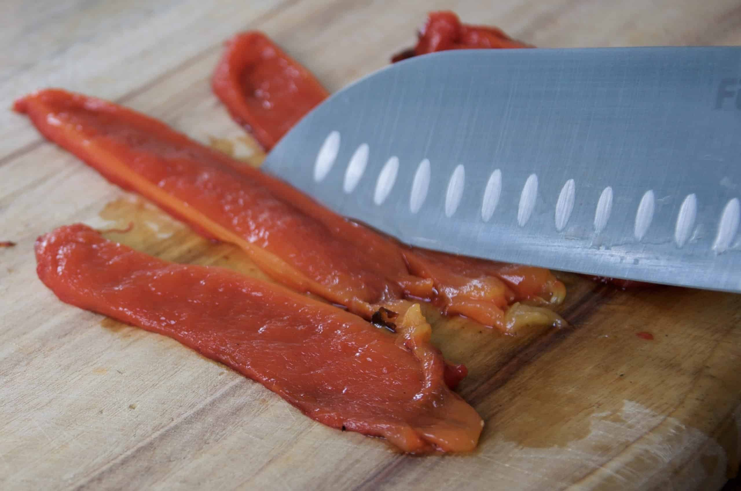 slicing chargrilled bell peppers/capsicum ready to use with silver knife