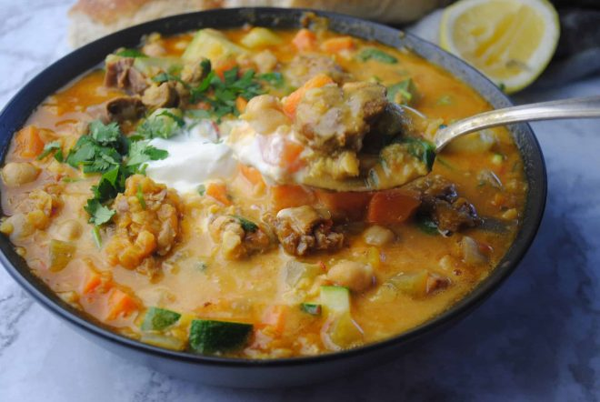 harira soup - spicy lamb, lentil and vegetable soup in black bowl dressed with coriander and yoghurt