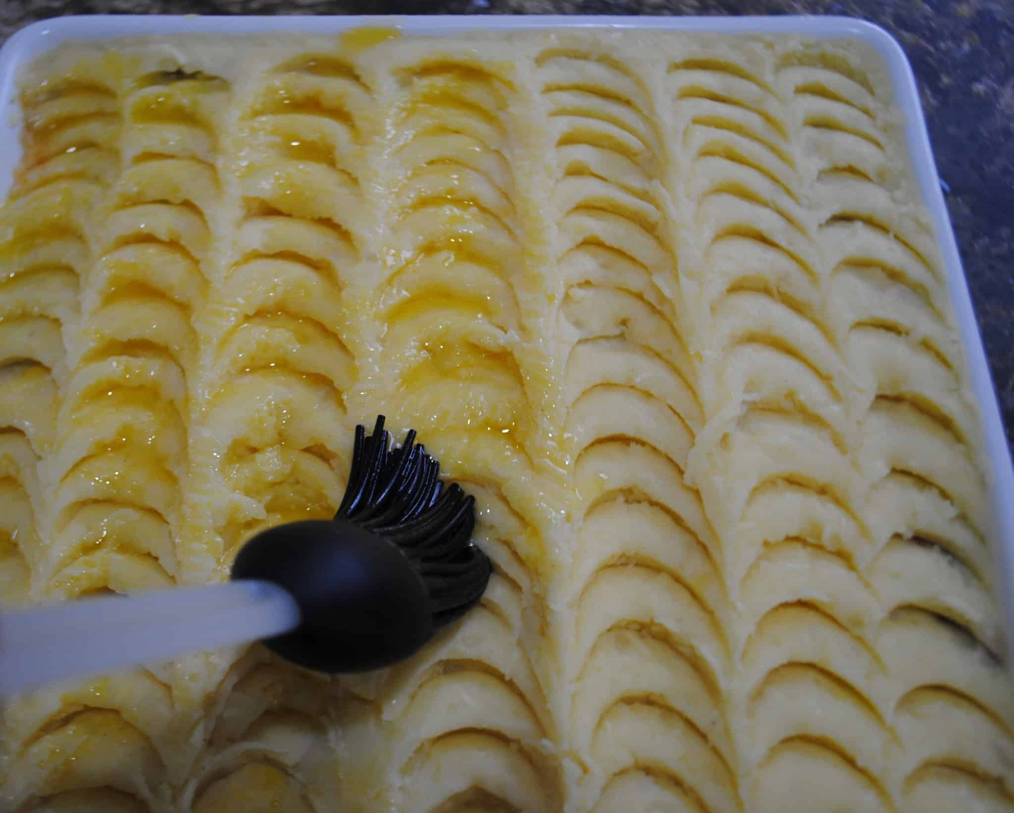 shepherds pie - brushing potatoes with butter using a pastry brush