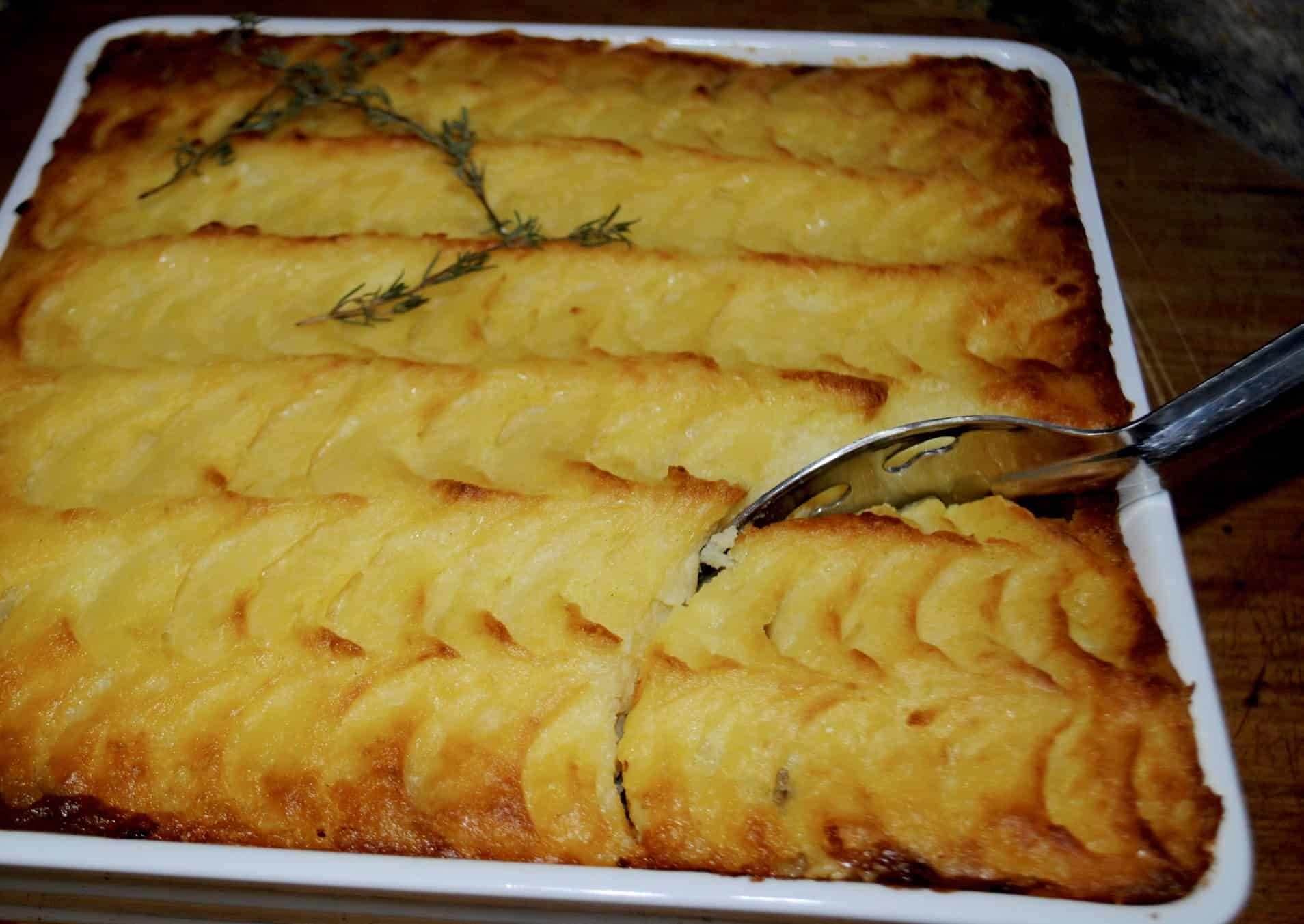 shepherds pie - pie fresh from oven with metal spoon cutting into the pie