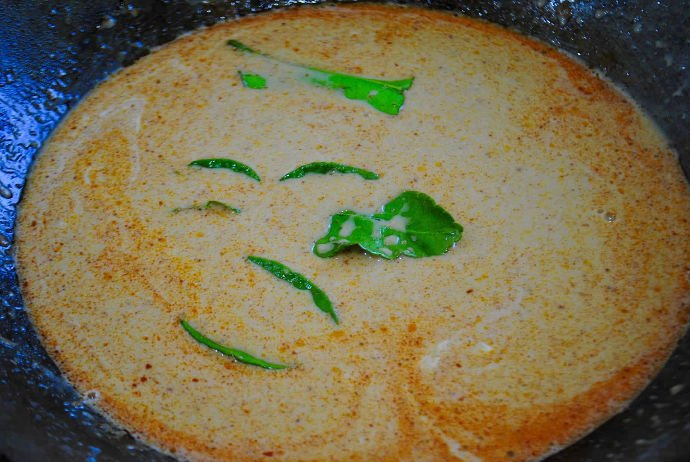 Thai vegetable red curry paste and coconut milk in a wok