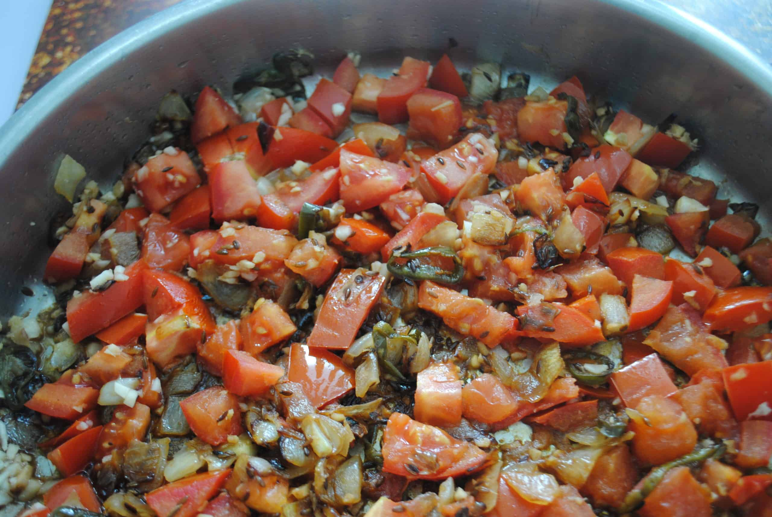 indian vegetable curry adding tomatoes, garlic and ginger to pan