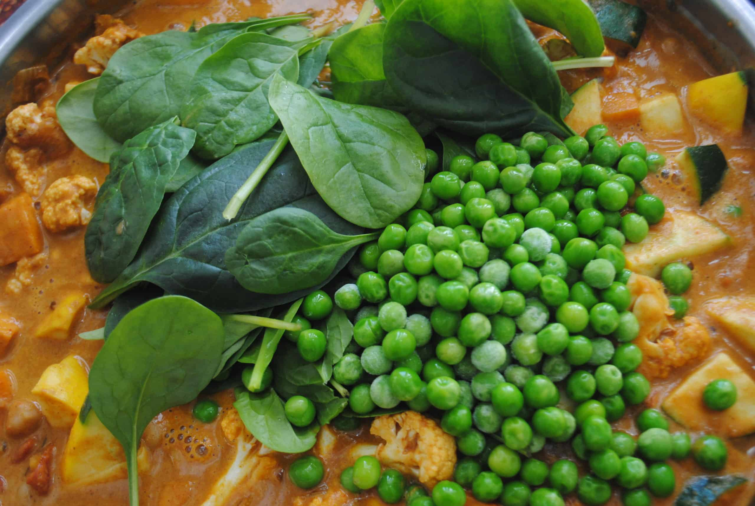 indian vegetable curry adding peas and baby spinach to wok
