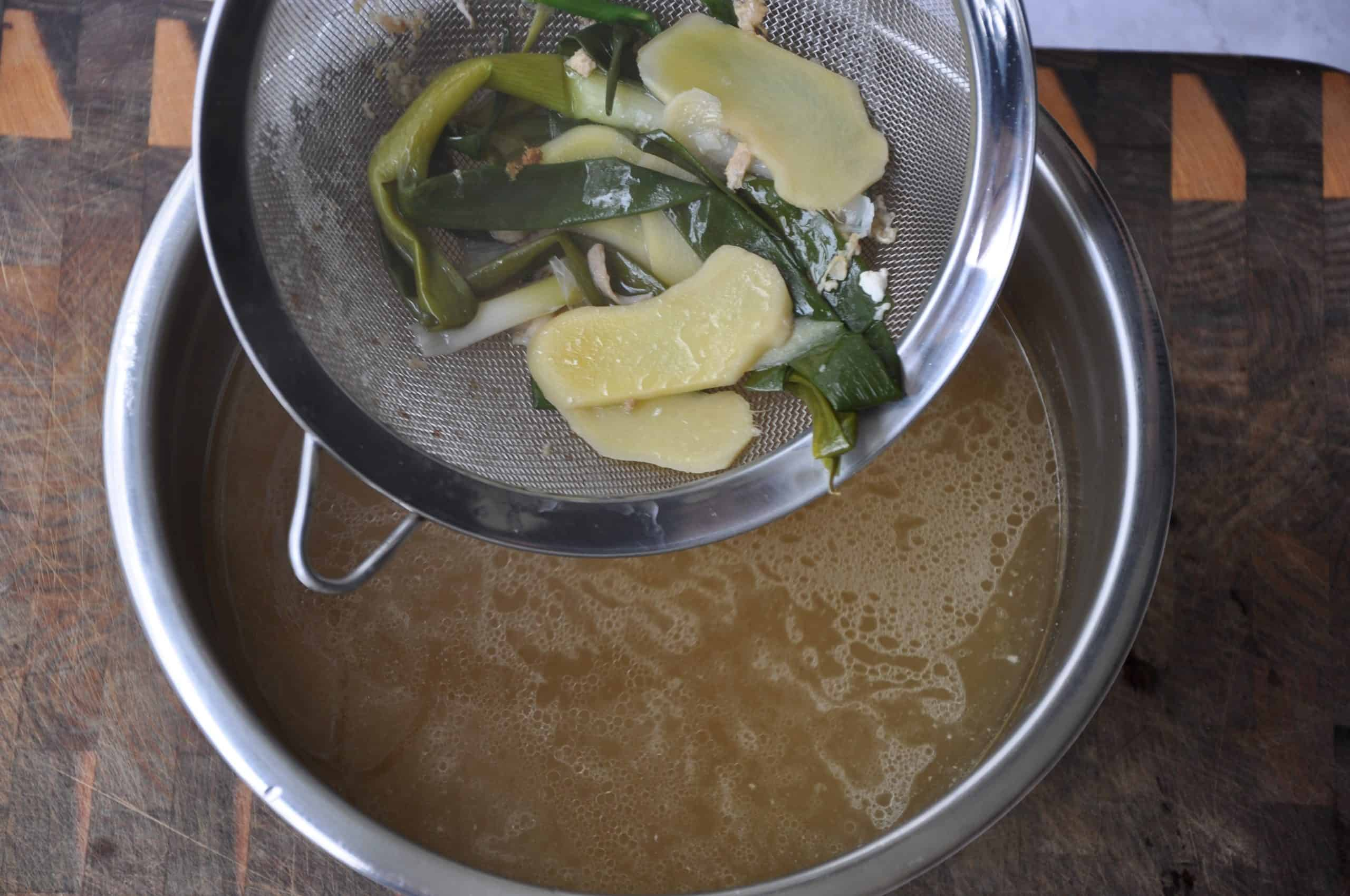 chicken and corn soup straining aromatics in sieve