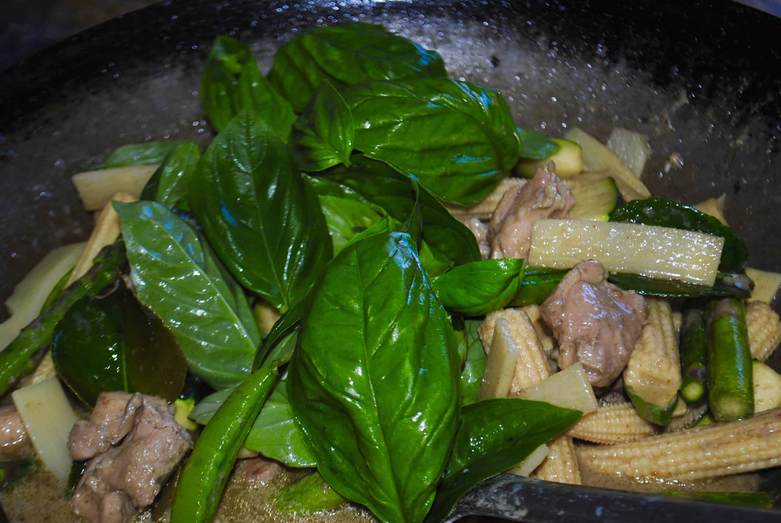 thai green chicken curry adding basil leaves before serving