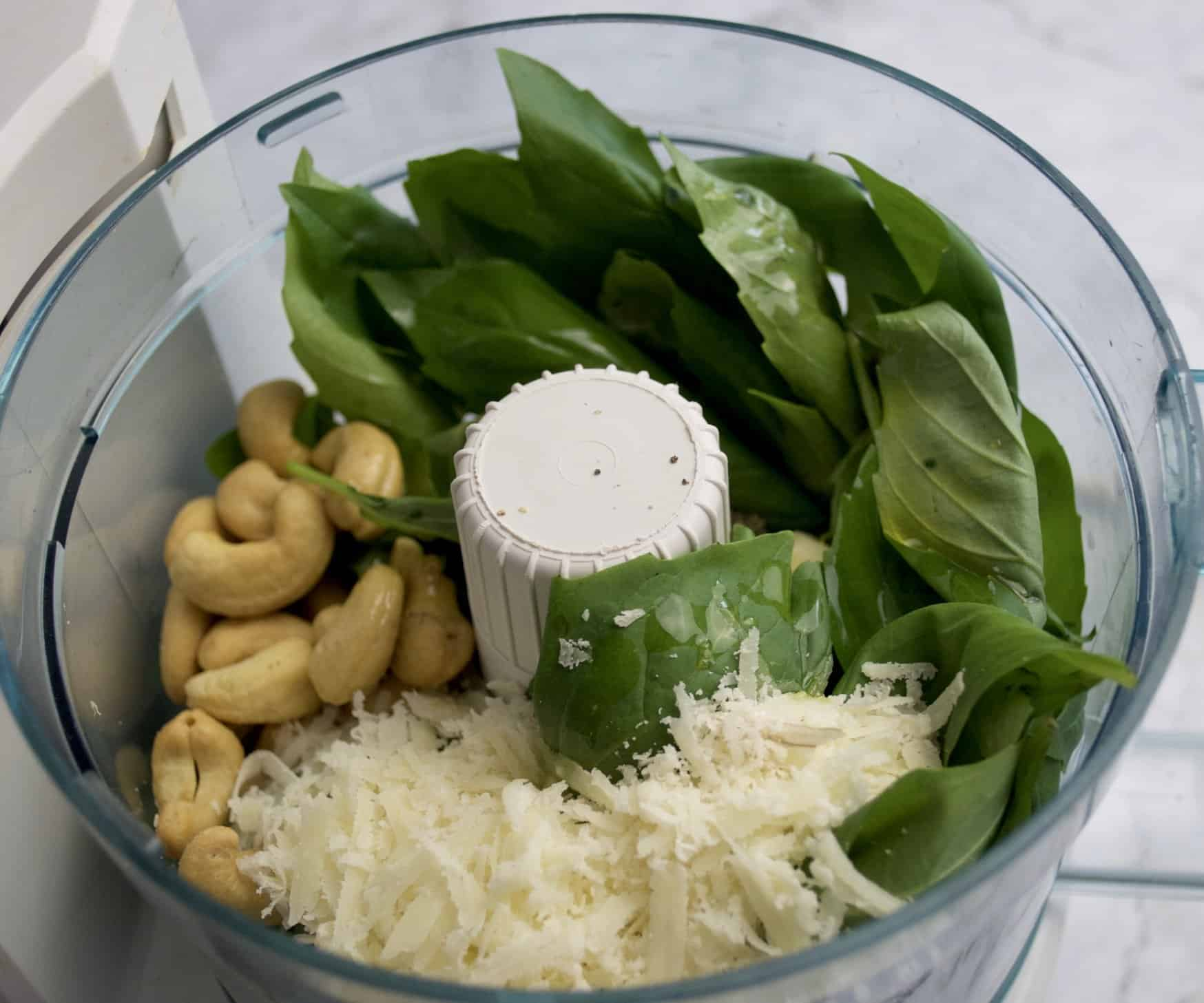 basil and cashew pesto ingredients in food processor