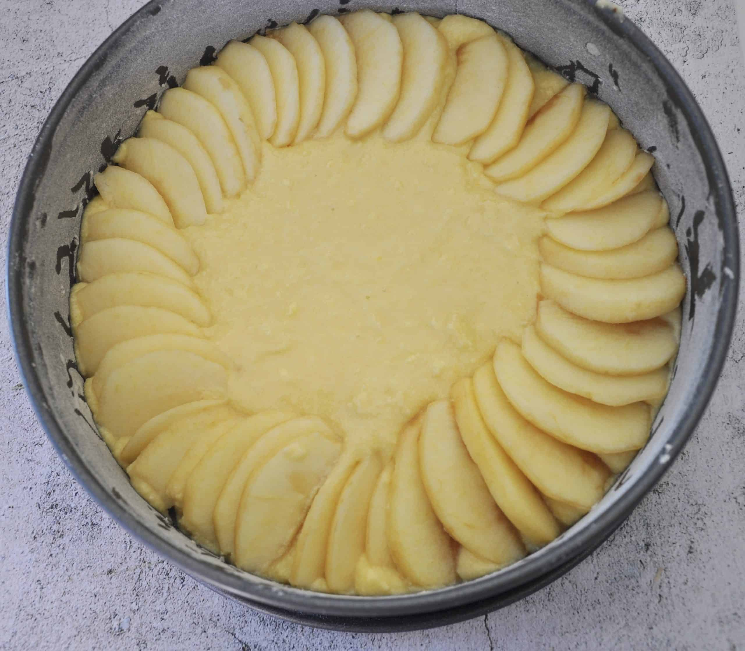 apple crumble cake layering apples starting from outside of floured cake tin