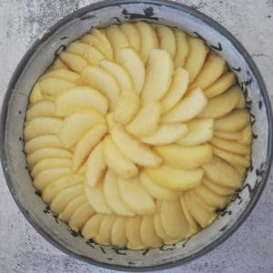 apple crumble cake apples finished layering on top of batter in floured cake tin