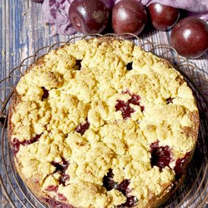 plum streusel cake baked sitting on a brown cake rack with fresh plums in the background