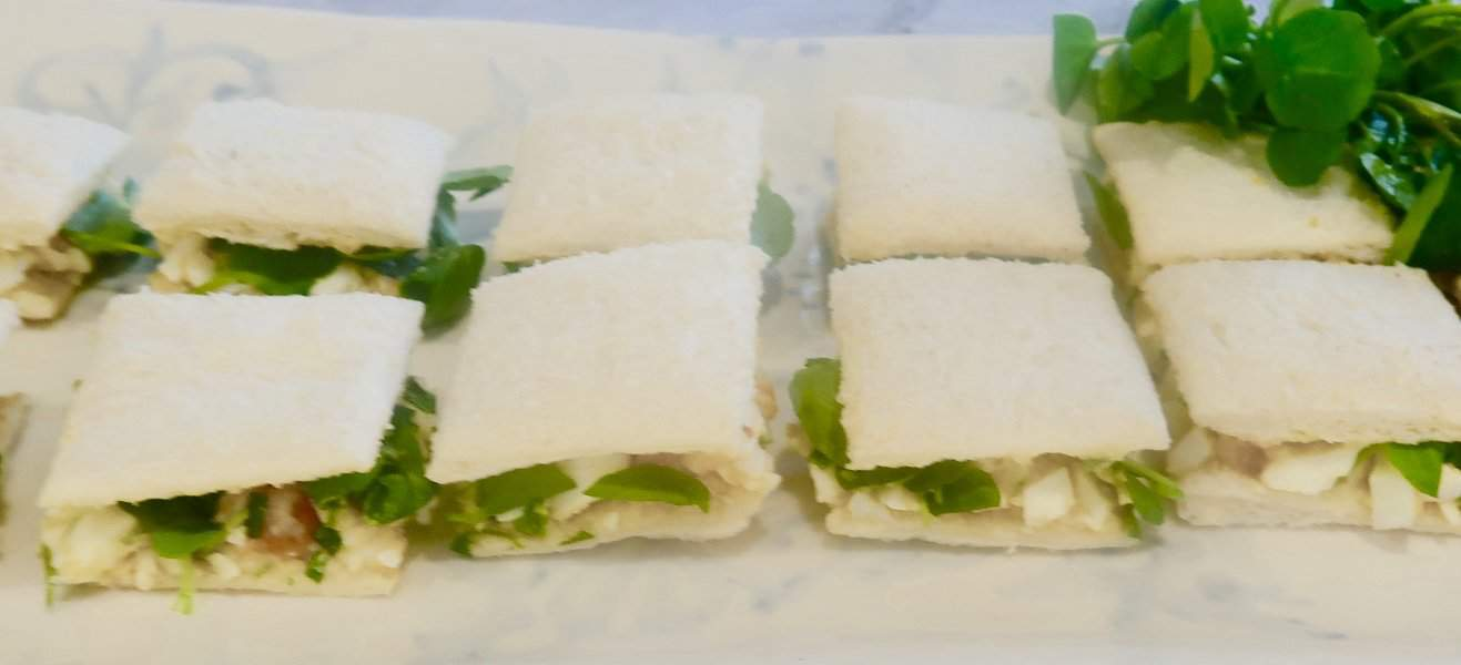 egg salad sandwiches cut into quarters on a white platter with watercress