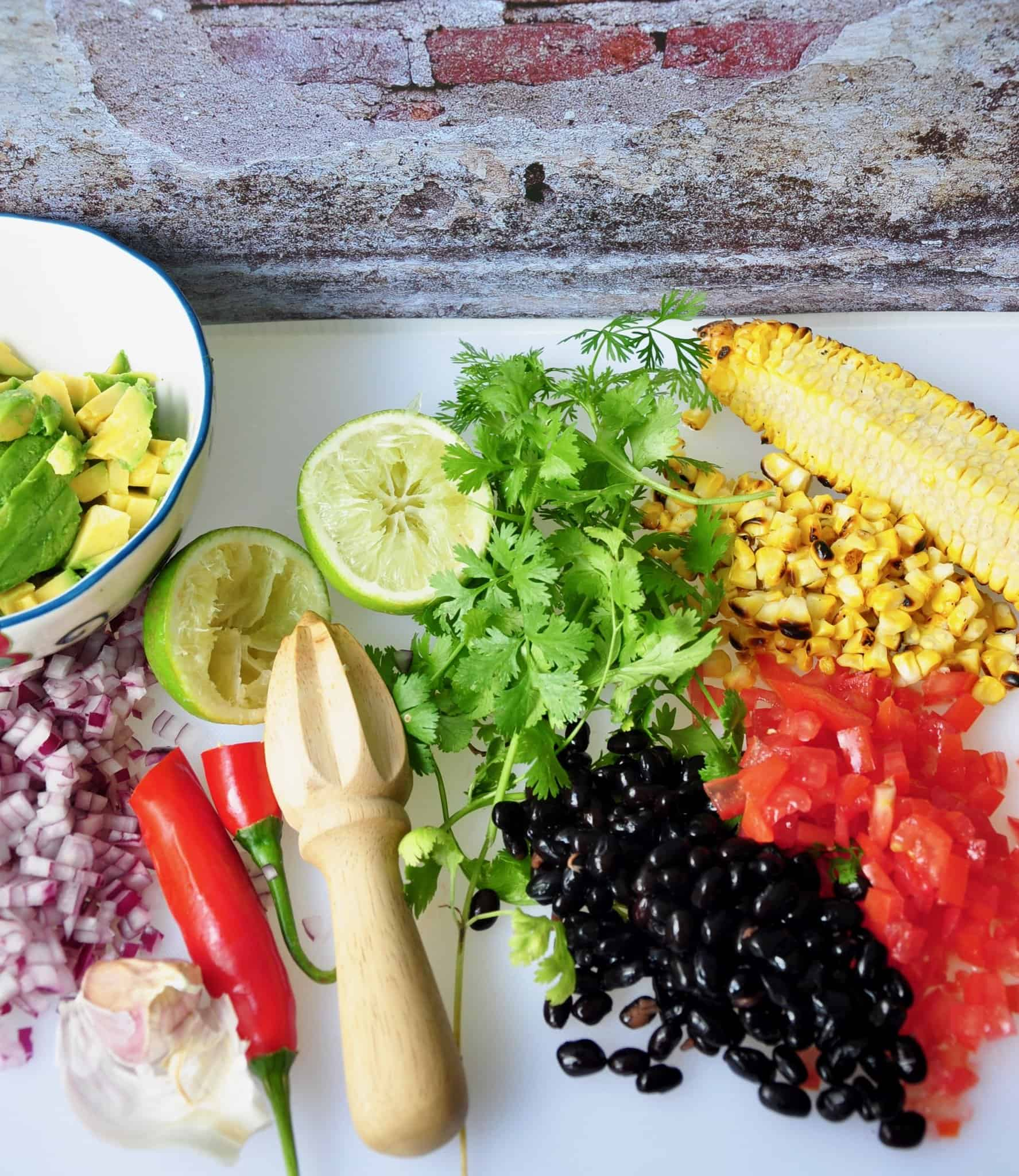corn salsa ingredients on a table with ingredients chopped