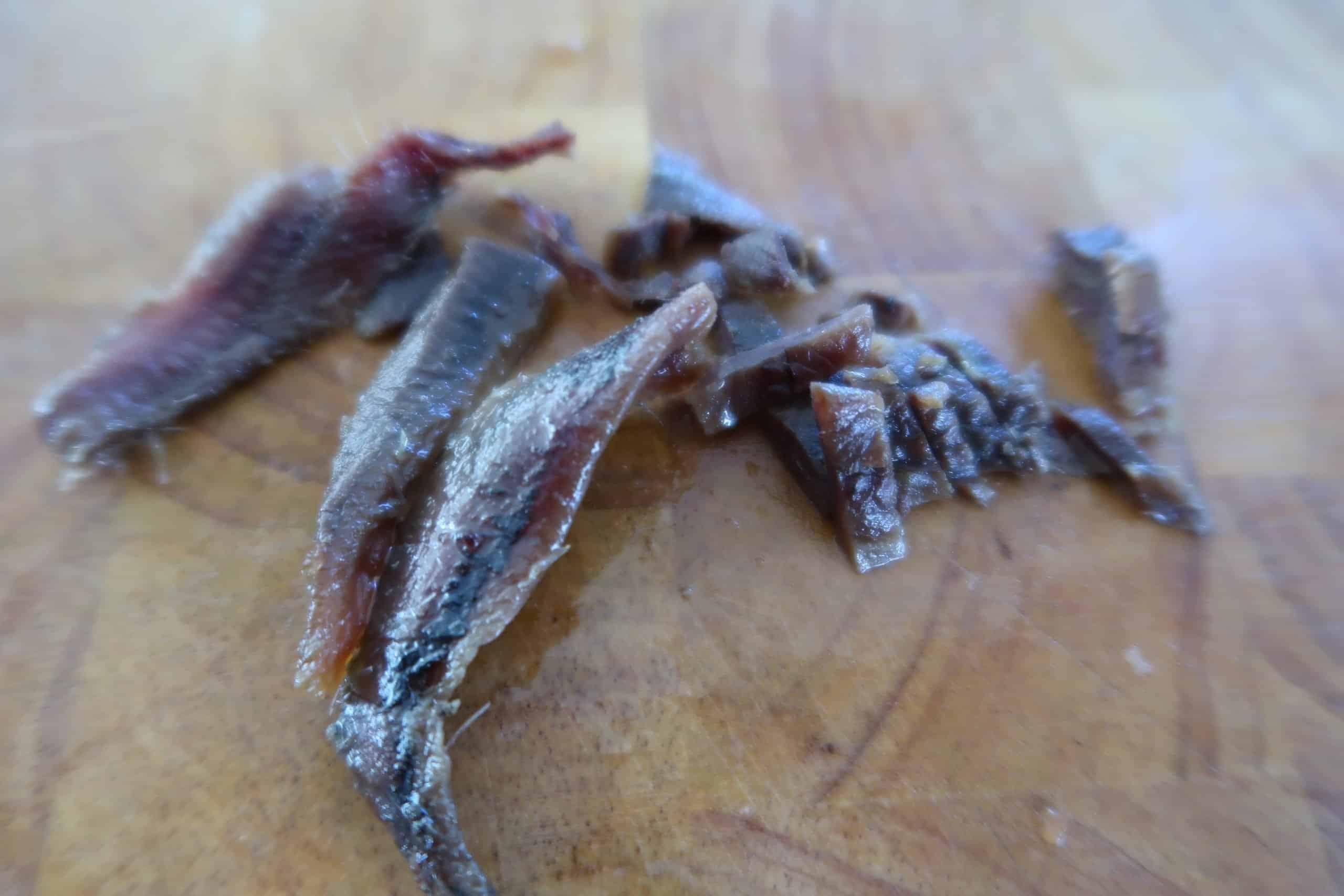 easy quick tuna pasta three anchovies on a wooden chopping board