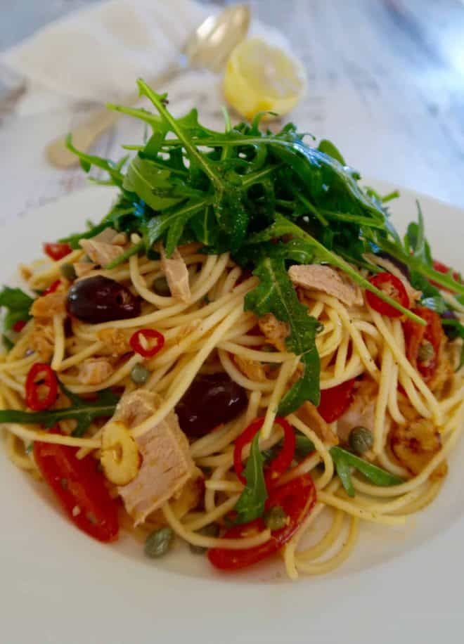 quick tuna pasta served on a white plate with fresh rocket on top of pasta and cut lemon in the background