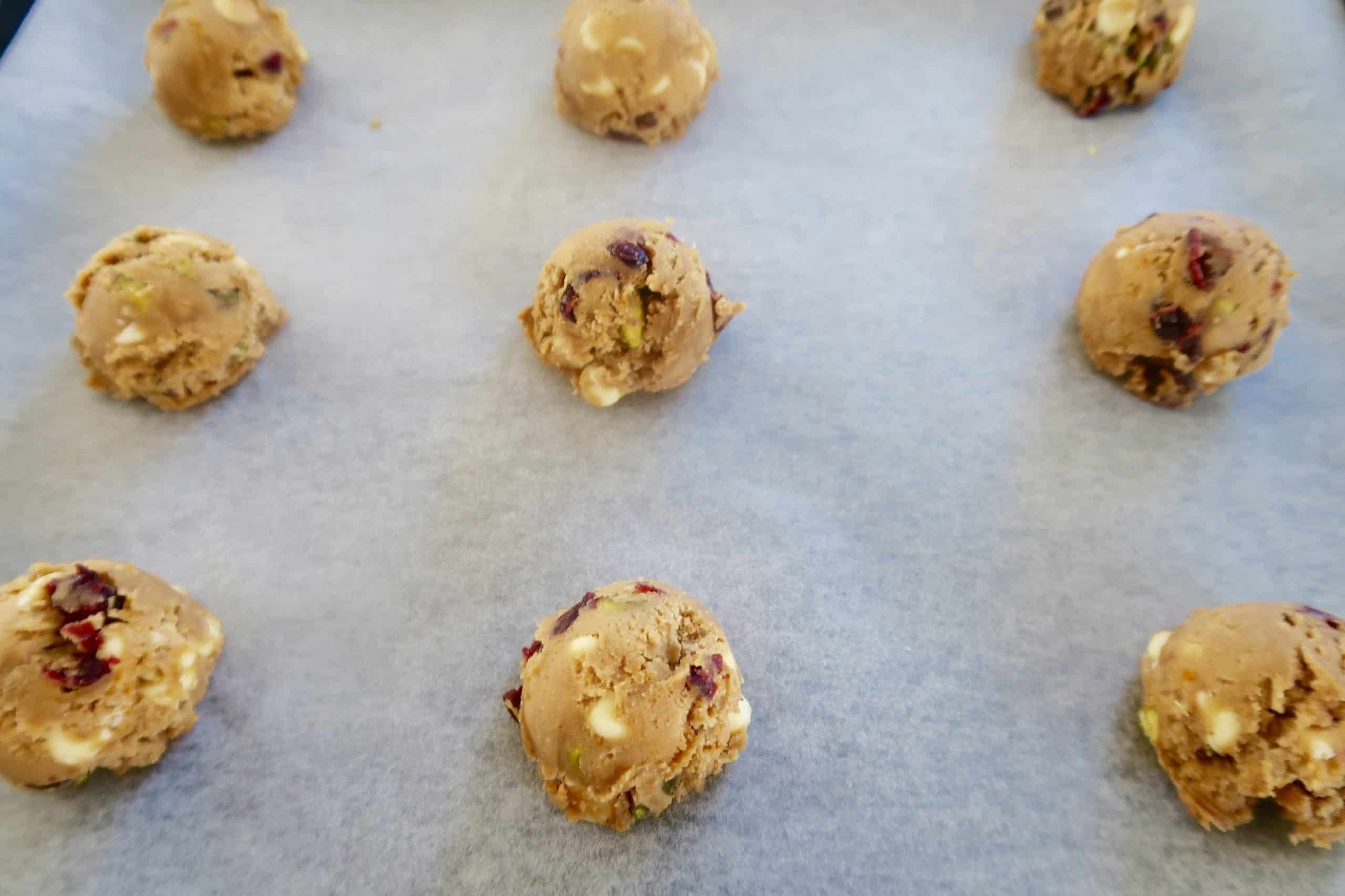 cranberry, white chocolate and pistachio cookies scooped into a ball and placed on baking paper on a cookie sheet