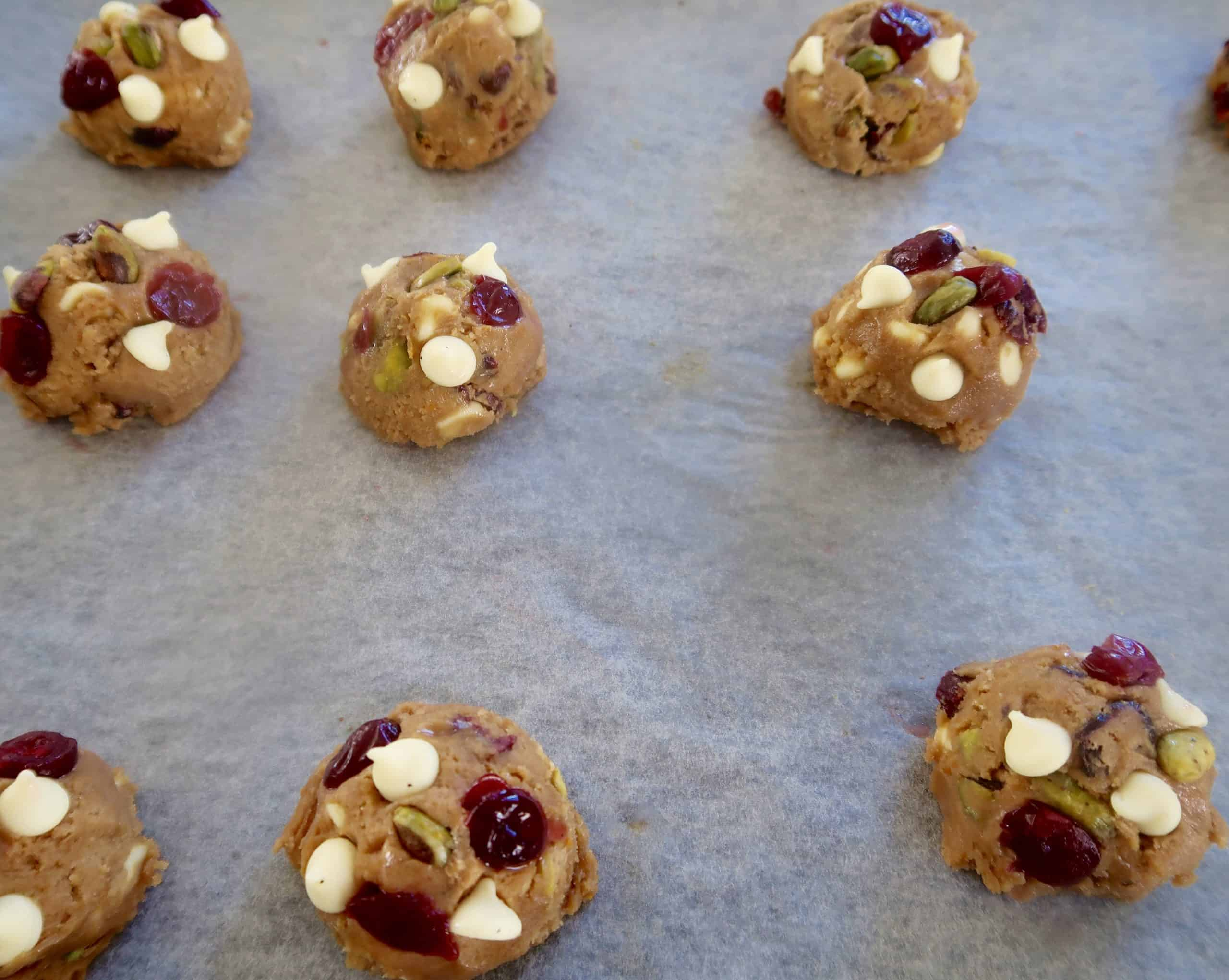 cranberry, white chocolate and pistachio cookies scooped out on baking paper with extra cranberries, pistachio and white chocolate buttons added to cookie