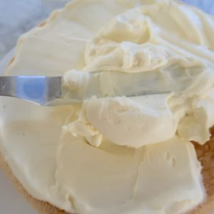 strawberry sponge cake spreading whipped cream onto bottom layer with metal spatula