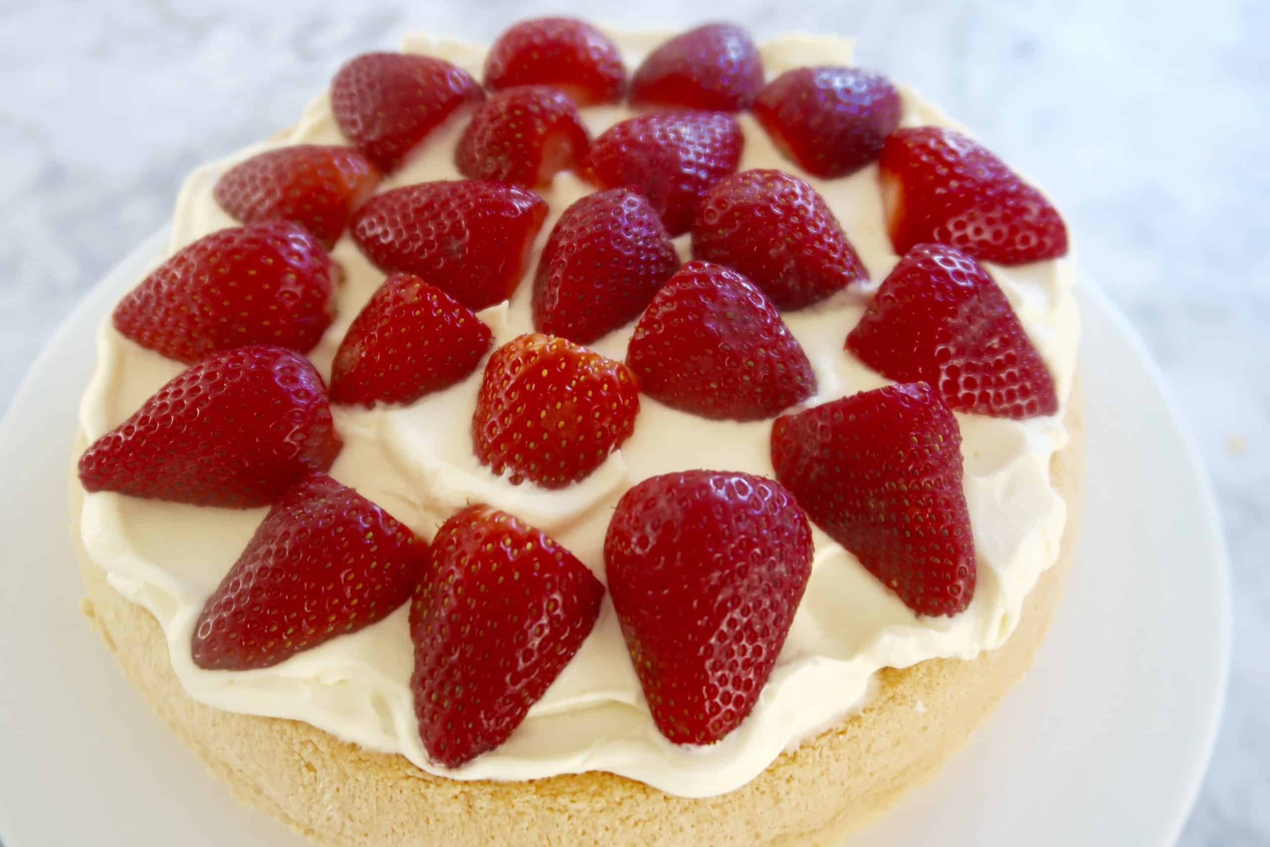 strawberry sponge cake spread with cream and topped with halved strawberries