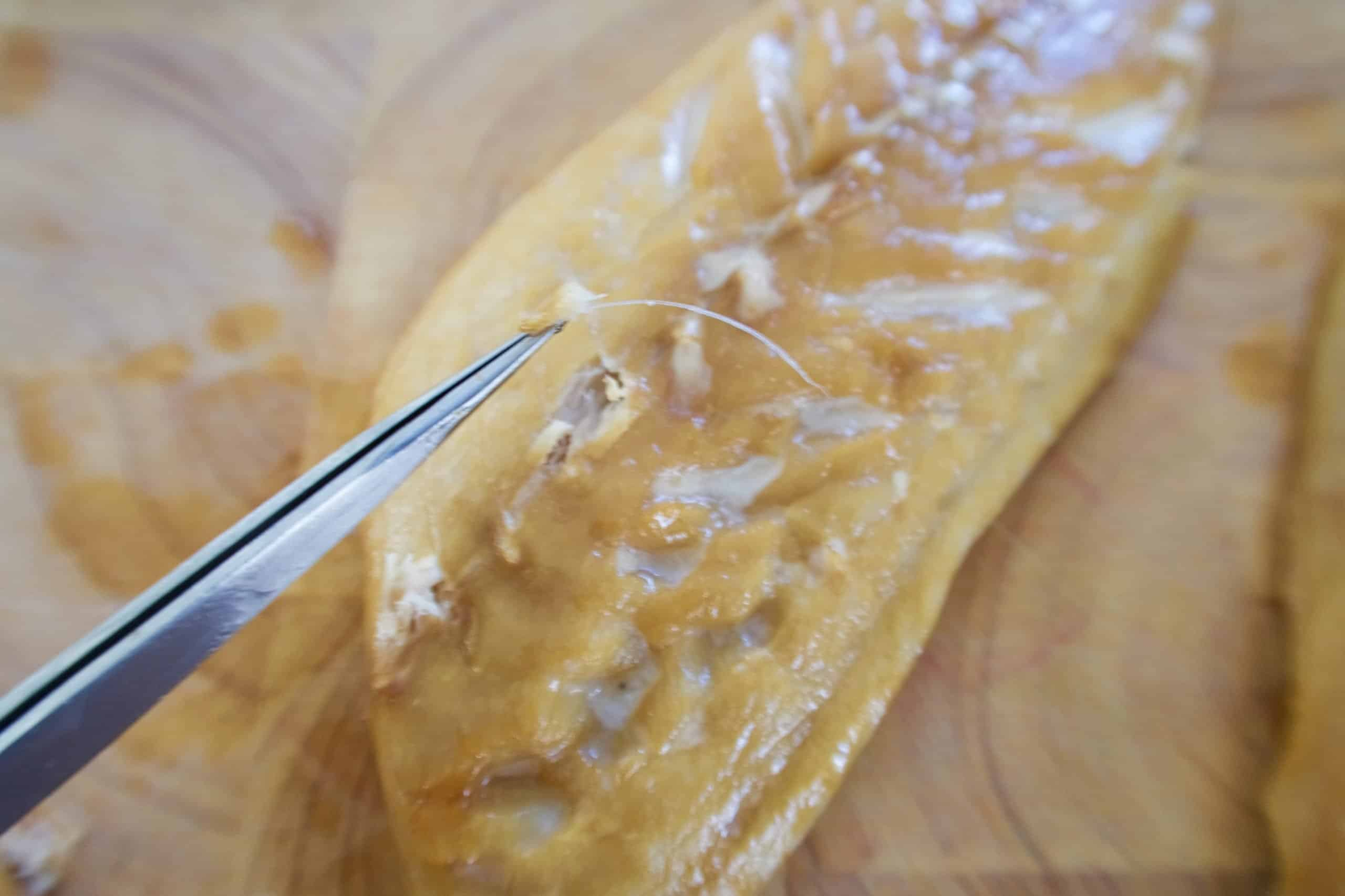 smoked mackerel pate removing fine bones from fillets with tweezers on a wooden chopping board