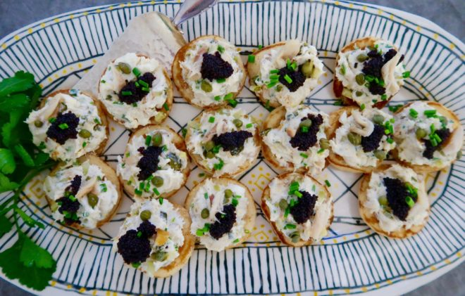 smoked mackerel pate served on a oval platter with black stripes and garnished with black caviar