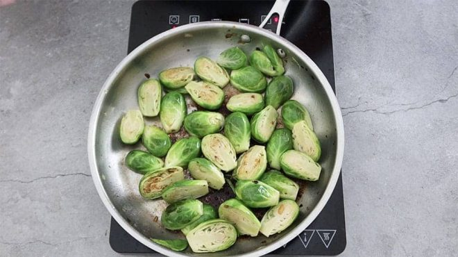 silver pan showing sprouts cooking to make Quick Brussel Sprouts with Bacon Onion and Garlic