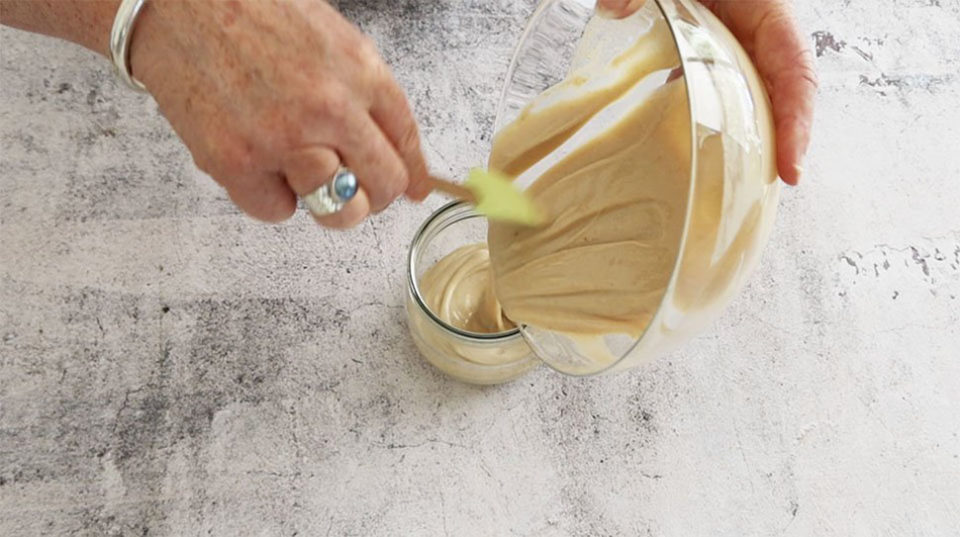 Pouring the condensed milk mayonnaise into a jar ready to store in the fridge