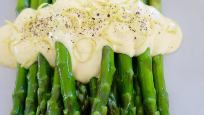 asparagus with hollandaise served on a white plate with a band of hollandaise sauce sprinkled with black pepper and lemon zest