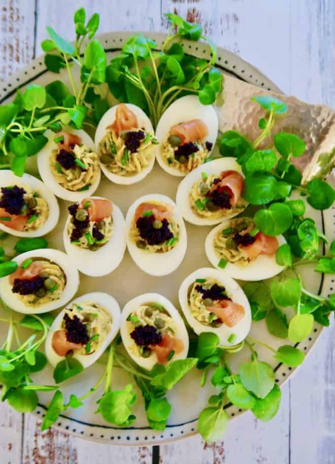 Deviled eggs with smoked salmon are a terrific holiday season finger food served with water cress on a silver tray