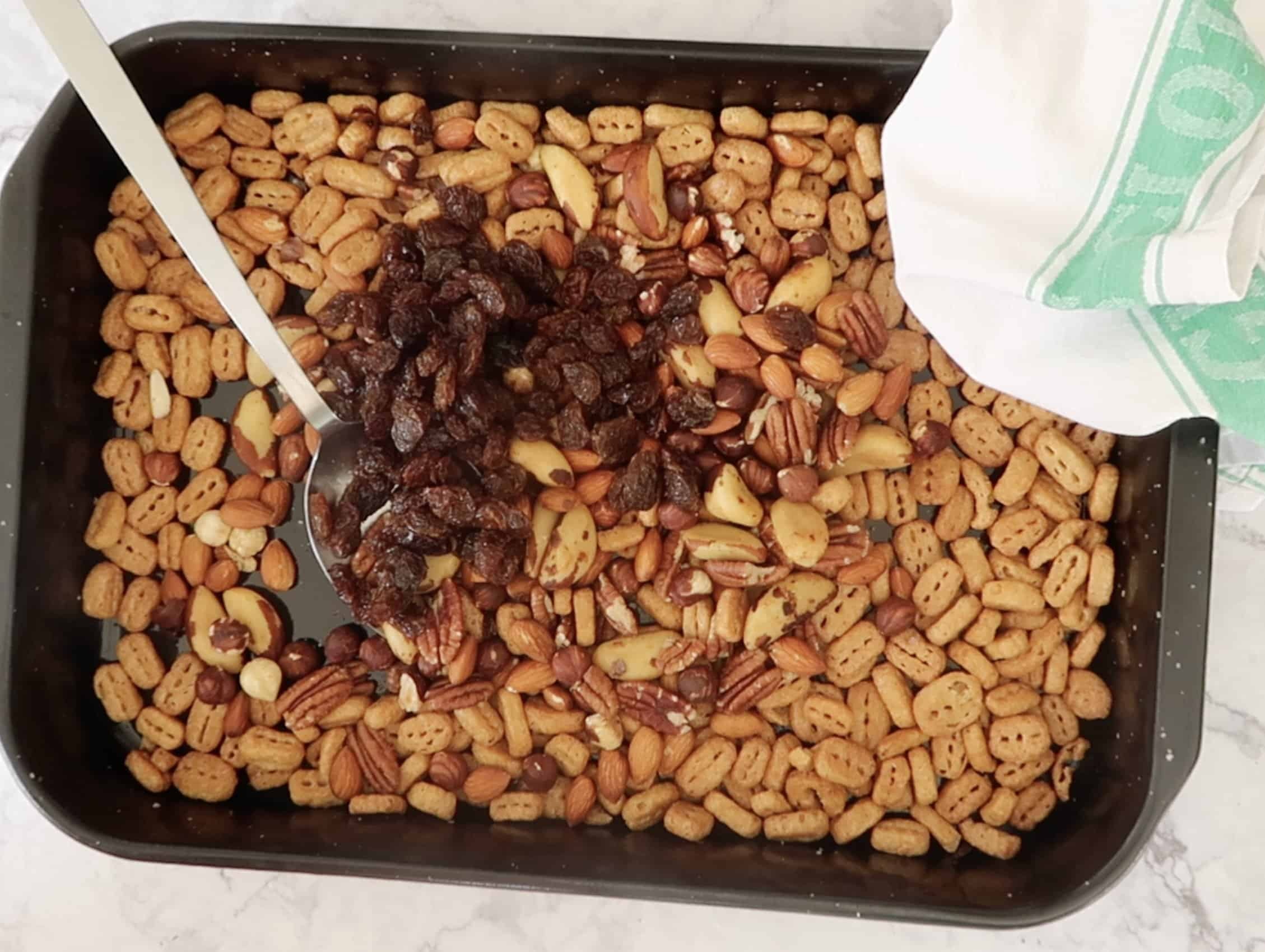 Nutty bolts on a baking dish of roasted Nutri Grain with a metal spoon and mixed nuts and raisins added to make nuts and bolts