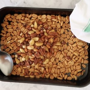 black baking dish of roasted Nutri Grain with a metal spoon and mixed nuts added to make nuts and bolts