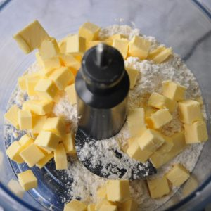 Butter and flour in a food pro bowl ready to blitz to make sour cream pastry for the Italian lemon mascarpone tart