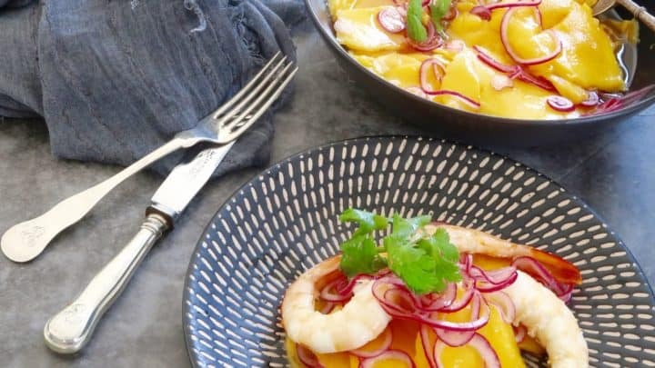 mango and red onion salad served with some fresh prawns on a black striped plate with the main bowl of salad in the background