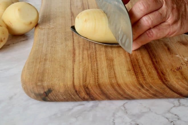 easy crispy hasselback potatoes slicing a whole potato which is sitting on a large kitchen spoon