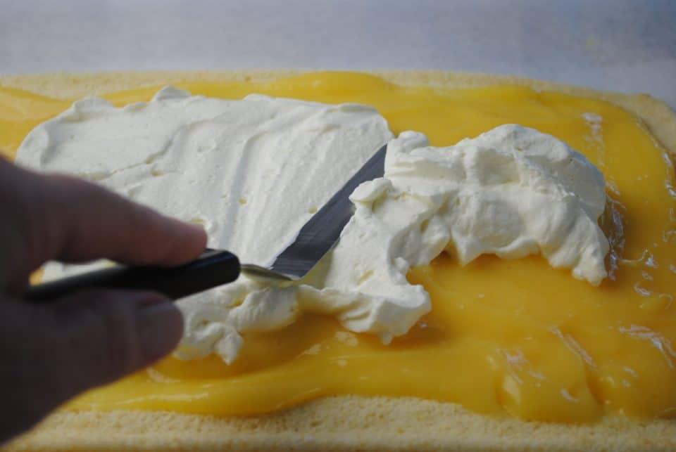 Spreading cream over lemon curd on sponge roulade