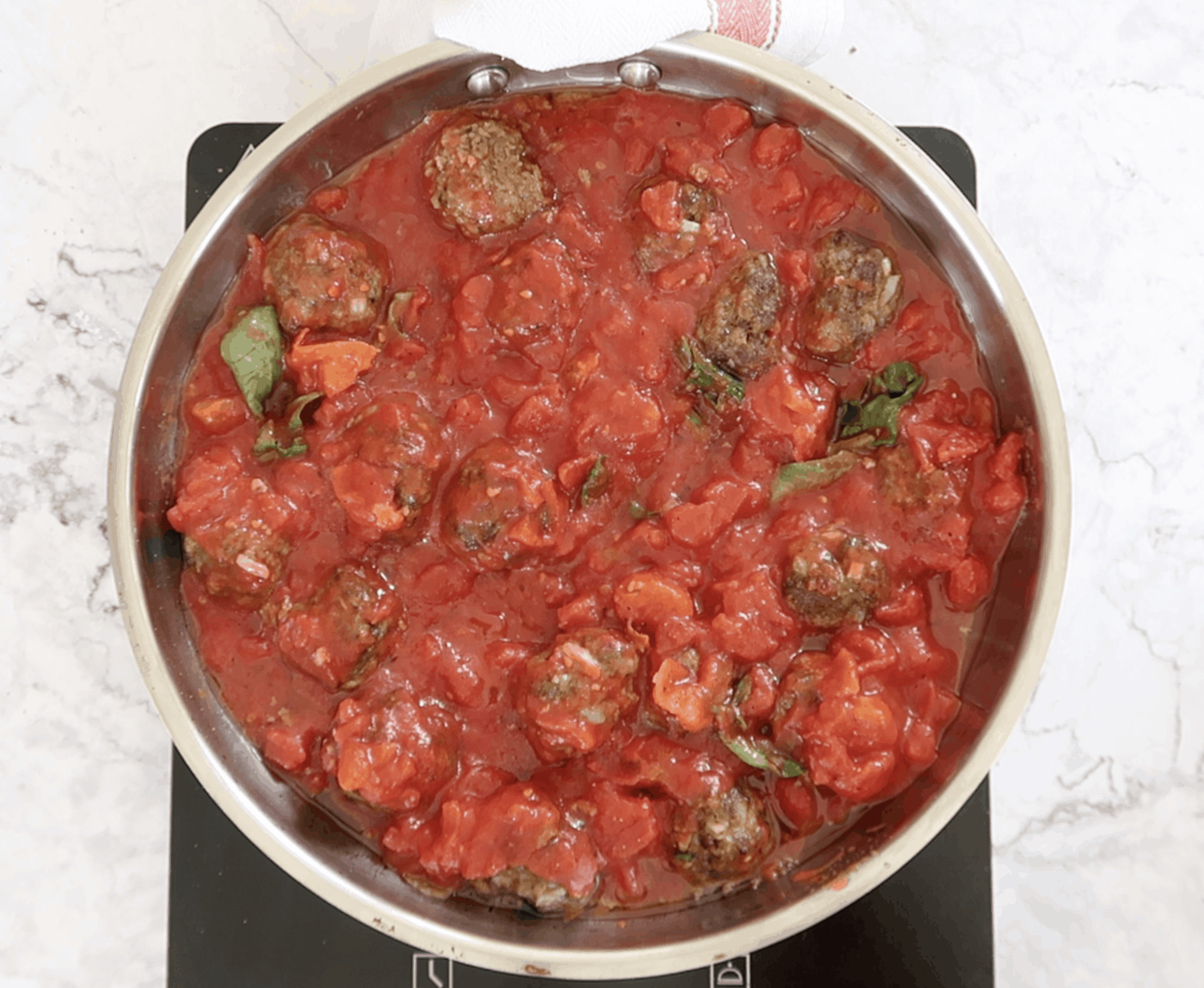 Italian Baked Meatballs with Tomato Sauce cooked in a silver frying pan