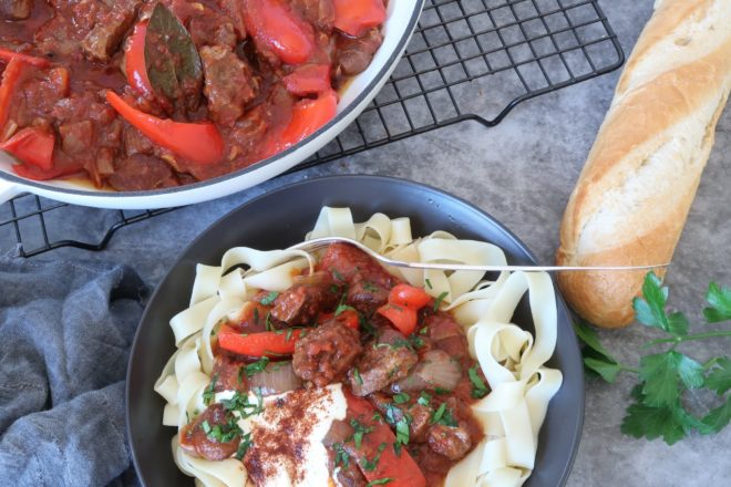 Beef Goulash served in a black bowl with crusty bread