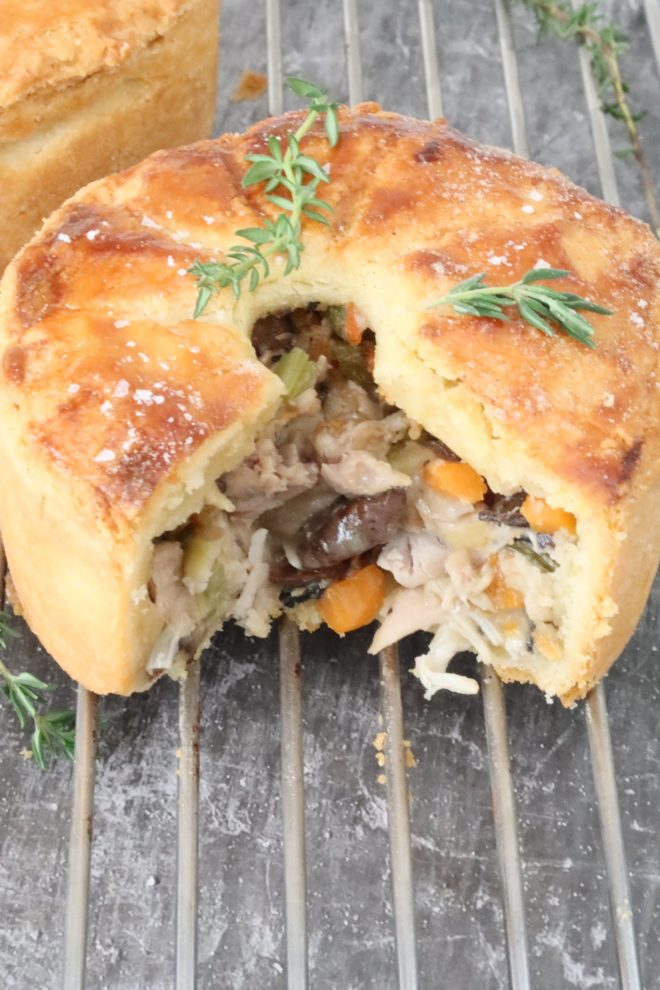 chicken, leek and mushroom pie cut and showing the filling on a wire rack with sprigs of thyme