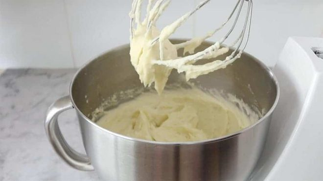 Whipped Creamy Mashed Potatoes in a stainless steel bowl with a beater covered in potatoe
