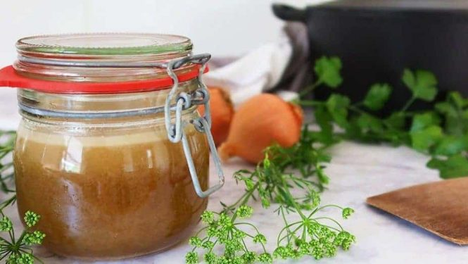 Intense Chicken or Turkey Stock in a jar with parsley and onions in the background