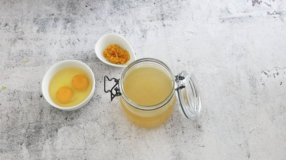 glass jar filled with stock on a concrete table with eggs and orange zest in seperate bowls to make Mum's Simple Classic Turkey Stuffing