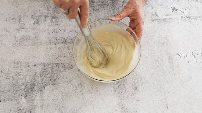 Beating the condensed milk mayonnaise in a glass bowl with a whisk