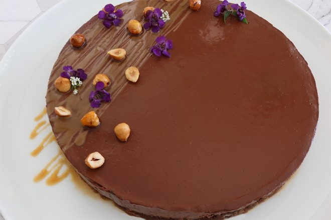 Upside Down Chocolate Crumble Tart served on a white plate with nuts and small purple flowers as a garnish