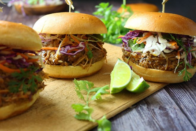 slow cooked pulled pork added to burger buns with lime wedges on the timber plate