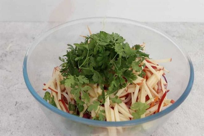 ingredients in a glass bowl ready to combine for quick and easy apple slaw
