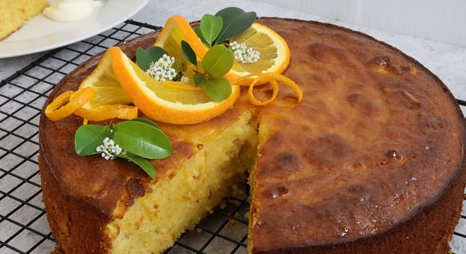 Orange and Almond Cake resting on a wire rack decorated with oranges and leaves