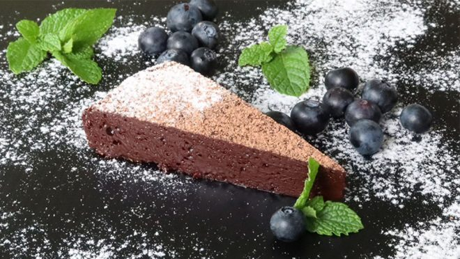 Chocolate Nemesis Cake on a dark plate with blueberries is perfect as part of our Mother's Day Dessert Collection