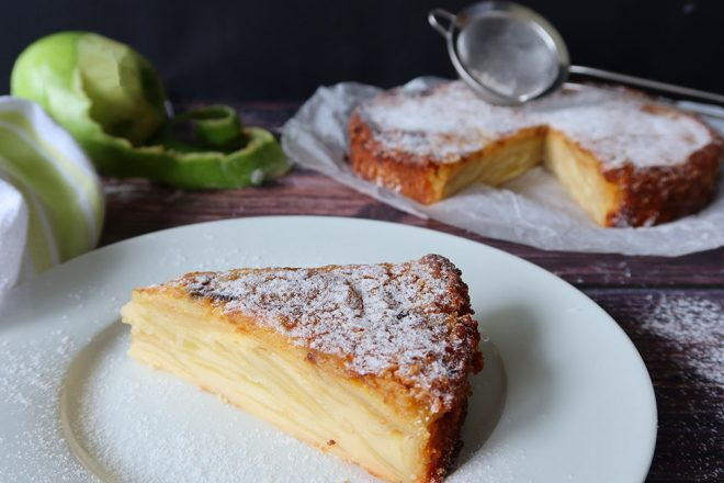 French Apple Cake slice on a white plate with the full cake in the backgrouns