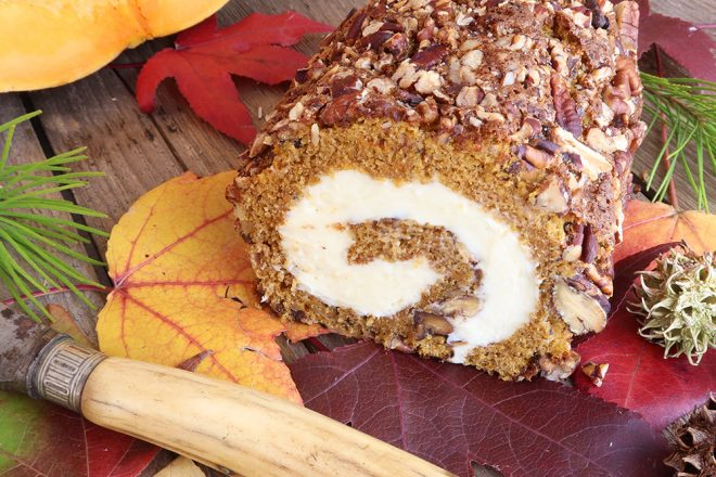 Pumpkin Spice Roulade Cake Recipe (with Pecan Nuts) resting on autumn leaves