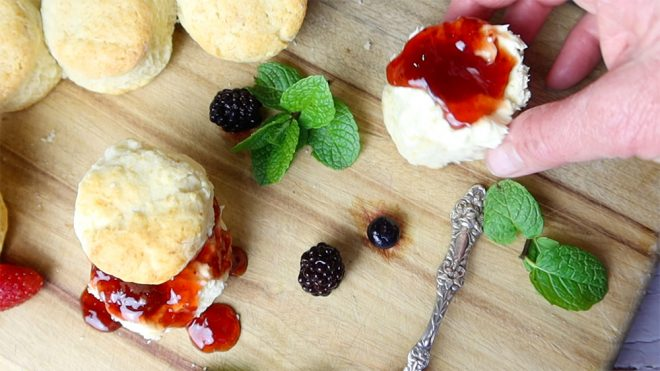 hand taking a cream and jam covered English scone