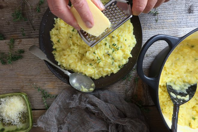 grating cheese over Risotto Milanese
