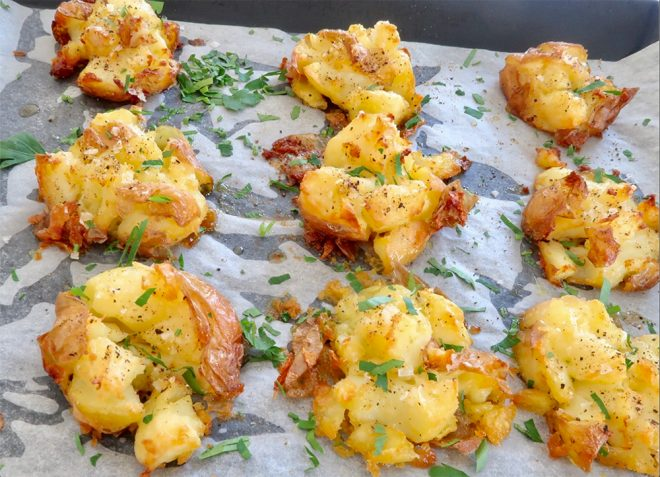 Crispy Smashed Roast New Potatoes on a baking tray garnished with parsley